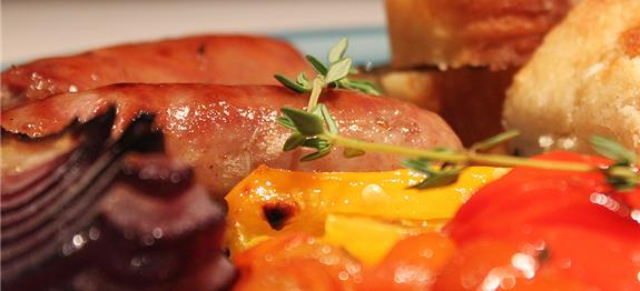 Sausages baked in an oven tray with peppers, red onions and cherry ...